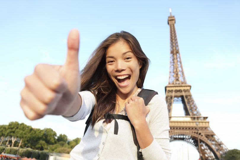 Paris Eiffel tower tourist happy backpacking in Europe. Cheerful smiling woman tourist showing thumbs up success sign in front of Eiffel Tower, Paris. Beautiful Asian Caucasian female model.